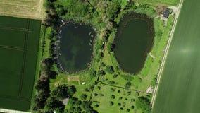 Vol au-dessus de champ et de lac agricoles - vue aérienne banque de vidéos