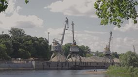 Vol au-dessus de port de récipient de Hambourg avec des bateaux et des grues au coucher du soleil banque de vidéos