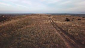 Vol au-dessus de route de campagne par la terre sèche et les collines banque de vidéos