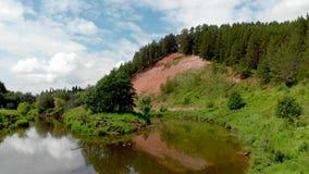 Vol au-dessus des montagnes, des forêts et de la rivière Photographie aérienne de Quadrocopter banque de vidéos