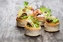 Vol-au-vents puff pastry cases filled with salted squid and oct royalty free stock images