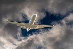 Vol blanc de jet d'avion par un trou en nuages de tempête dangereux et dramatiques foncés photo libre de droits