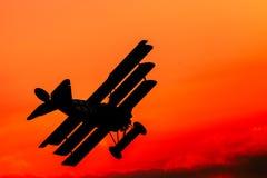 Vol classique d'avion sur un ciel rouge dans la lumière de soirée Images stock
