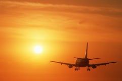 Vol commercial d'avion à réaction dans le coucher du soleil Image libre de droits
