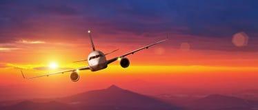 Vol commercial d'avion au-dessus des montagnes dans le coucher du soleil Images stock