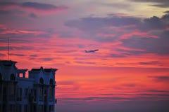 Vol d'aéronefs dans le coucher du soleil rouge Photo stock