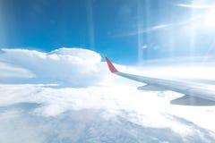 Vol d'aile d'avions au-dessus des beaux nuages avec la lumière du soleil dedans Photographie stock