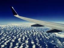 Vol d'aile d'avion au-dessus des nuages Photographie stock libre de droits