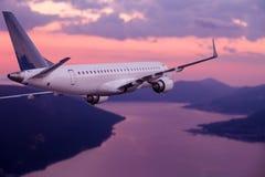 Vol d'avion au coucher du soleil pourpre au-dessus des montagnes et de la mer Photo stock