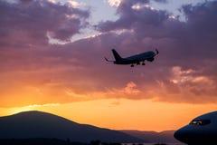Vol d'avion au coucher du soleil pourpre au-dessus des montagnes et de la mer Images libres de droits
