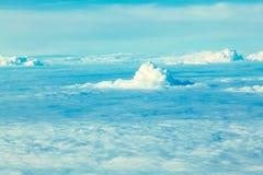 Vol d'avion dans le ciel bleu parmi les nuages blancs photographie stock