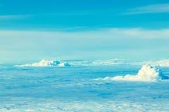 Vol d'avion dans le ciel bleu parmi les nuages blancs images stock