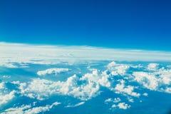 Vol d'avion dans le ciel bleu parmi les nuages blancs photographie stock libre de droits