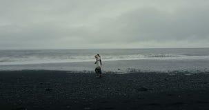 Vol d'hélicoptère près des jeunes couples dans le chandail islandais Marche d'homme et de femme, tenant des mains sur la plage vo clips vidéos