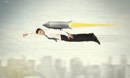Vol d'homme d'affaires de super héros avec la fusée de paquet de jet au-dessus du CIT image stock
