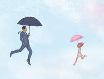 Vol d'homme et de femme en air ouvert avec des parapluies Photographie stock libre de droits