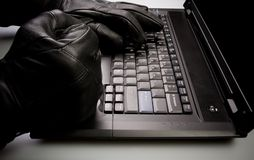 Vol d'identité, intrus travaillant sur l'ordinateur portatif Photographie stock libre de droits