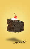 Vol d'isolement de gâteau de cerise de chocolat sur le fond jaune Images libres de droits