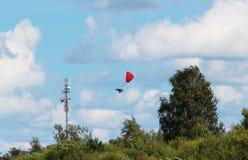 vol dangereux de paramotor autour de la tour avec les antennes paraboliques et les antennes Photo stock