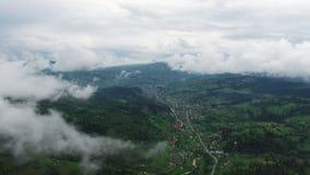 Vol dans les nuages Une vue de la terre par les nuages Une route de montagne d'enroulement La route est sur les tailles du clips vidéos