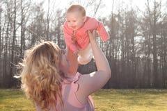 Vol de bébé en nature quand la maman la tient Photos stock