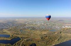 Vol de ballon à air chaud au-dessus de paysage rural Image stock