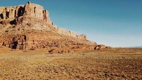 Vol de bourdon au-dessus de désert de grès vers la montagne rocheuse énorme dans le vaste paysage sec américain de région sauvage banque de vidéos