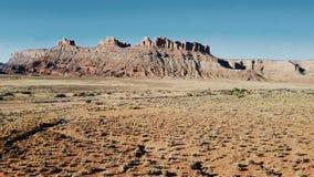 Vol de bourdon au-dessus de désert sec de grès vers la montagne stupéfiante de surface plane et le ciel bleu clair en parc nation banque de vidéos