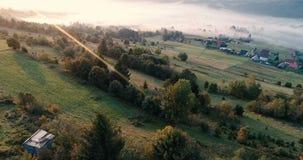Vol de bourdon au-dessus de village de montagne brumeux rêveur pendant le lever de soleil clips vidéos