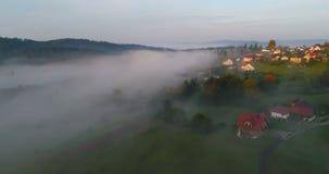 Vol de bourdon au-dessus de village de montagne brumeux rêveur pendant le lever de soleil banque de vidéos