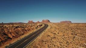Vol de bourdon laissé au-dessus du tour vide de route de route de désert de grès en vallée de monuments, Arizona avec les montagn banque de vidéos