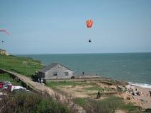 Vol de cerf-volant de photo faisant un saut en chute libre au-dessus de la baie occidentale Dorset Photographie stock
