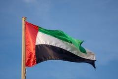 Vol de drapeau des EAU dans le ciel bleu photos libres de droits