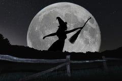 Vol de silhouette de sorcière de Halloween avec le manche à balai Pleine lune Photos stock
