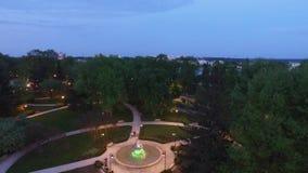 Vol de soirée au-dessus d'une fontaine lumineuse, vue aérienne banque de vidéos