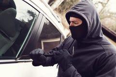 Vol de voiture - voleur essayant de diviser en véhicule photos stock