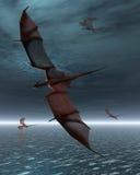 Vol des dragons rouges au-dessus de la mer Photographie stock