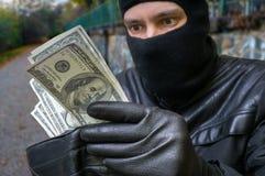 Vol du concept Le voleur masqué compte l'argent dans le walle volé photographie stock