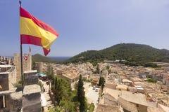 Vol espagnol de drapeau au-dessus de la ville de Capdepera sur Majorca Photographie stock libre de droits