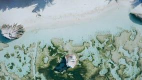 Vol hiérarchisé aérien de la vue 4k au-dessus des rochers épiques de granit dans l'eau calme de marée basse sur Anse plage a banque de vidéos