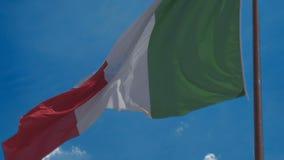 Vol italien patriotique de drapeau en vent sur le fond de ciel bleu, mouvement lent banque de vidéos
