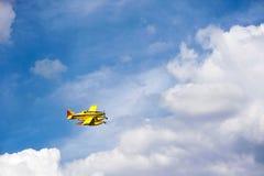 Vol jaune d'avion au-dessus des nuages Photos libres de droits
