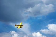 Vol jaune d'avion au-dessus des nuages Images libres de droits