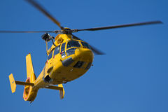 Vol jaune d'hélicoptère en ciel bleu Photo libre de droits