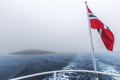 Vol norvégien de drapeau dans le vent au-dessus de la mer Photos stock