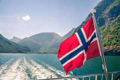 Vol norvégien de drapeau sur la plate-forme arrière du bateau de croisière de fjord image libre de droits