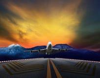 Vol plat d'avion de passagers au-dessus des pistes d'aéroport contre le beau ciel sombre Image stock