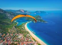 Vol tandem de parapentiste au-dessus de la mer avec l'eau bleue et le mounta Photo stock