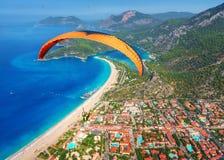 Vol tandem de parapentiste au-dessus de la mer avec l'eau bleue et le mounta Image stock