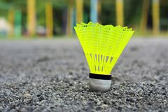 Shuttlecock with a white tip and a light green shank on the gaming, fenced net, site.  stock photo
